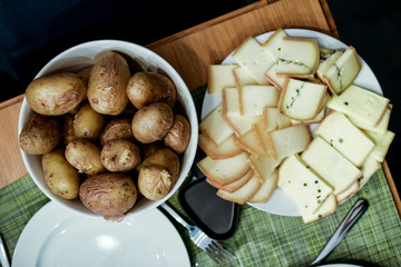 close up on slices of cheese and potatoes at raclette party