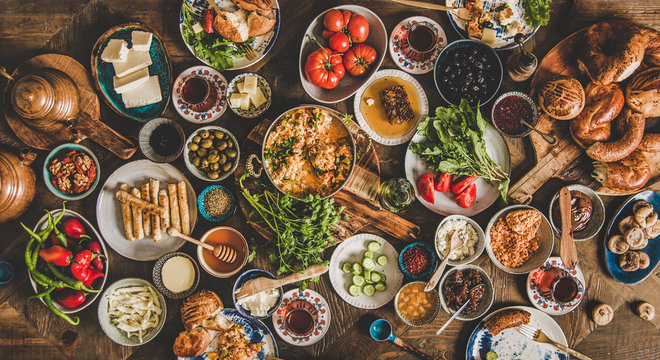 Turkish breakfast table. Flat-lay of fresh pastries, vegetables, greens, olives, cheeses, fried eggs, jams, honey, tea in copper pot and tulip glasses, top view. Middle Eastern meal