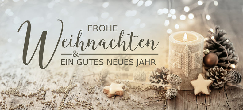 Christmas greeting card german text - Merry Christmas and happy new year - White burning candle with natural decoration on rustic light wood