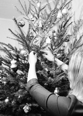 Girl decorating Christmas Tree in the House with Christmas Balls Decoration. Black and White Photo