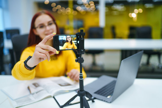 Hand woman holding camera for recording video while sitting at office. Teenager student in a yellow sweater with laptop having fun vlogging live feeds on social media. Technology and videoblog concept