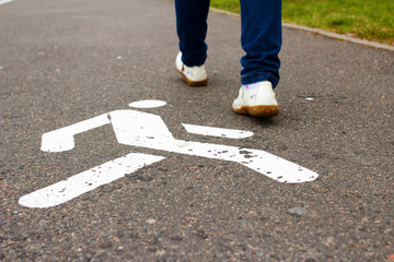 White pedestrian sign on sidewalk and feet of woman pedestrian