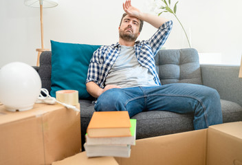 Man sitting on sofa with belongings in living room ready to move