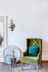 Chair in Moroccan style in white room with wooden floor. sunny light Interior