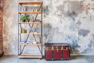 Book shelf and wooden chest in front of the grunge shabby gray wall. Interior background
