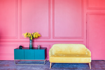 Bright color interior. Pink wall, yellow sofa and blue bedside table with flowers.