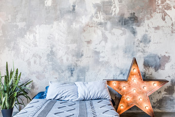 Grungy Shabby wall in bedroom. Star shaped lamp. Modern interior design.