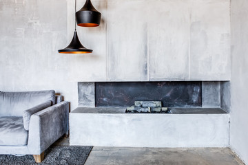 Fireplace and sofa in modern interior. Living room with gray concrete walls