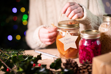 Putting Reusable Wooden Gift Tag On Homemade Jars Of Preserved Fruit For Eco Friendly Christmas Gift