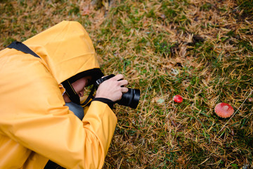 From above active person in yellow raincoat with hood taking photo of red amanita in grass in forest