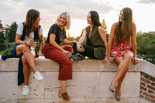 Group of happy women smiling and embracing each other while spending time in city park