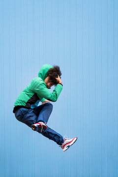 Cheerful curly ethnic male dancer in active blue wear jumping with crossed legs and covering face with hand on blue background