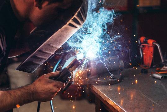 Professional welder in mask welding metal