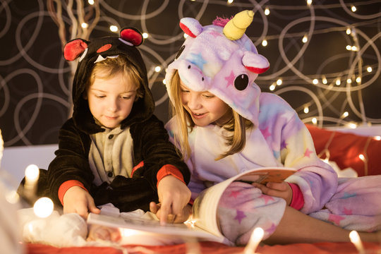 Cute little siblings in cozy kigurumi pajamas reading book with fairy tales while sitting together on bed decorated with Christmas lights