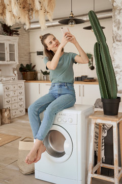 Chilling young barefoot woman having break and comfortably sitting on white washing machine surfing mobile phone in spacious kitchen