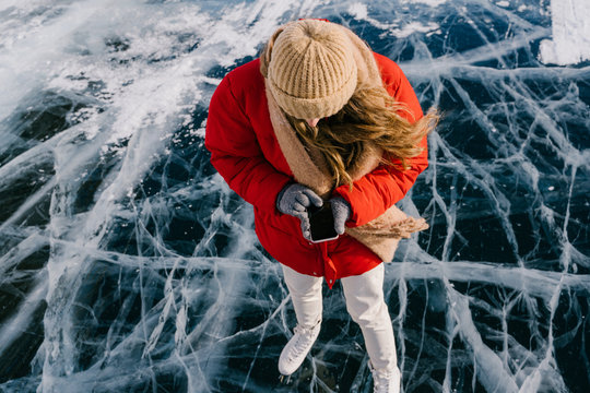 From above of modern active female in warm clothes and skates standing on dark cracked ice on frozen river and using smartphone on winter day in Siberia