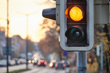 Closeup of traffic lights showing orange color to the traffic on the street during sunset. Seen in Nuremberg, Bavaria / Germany in December Fotomurales