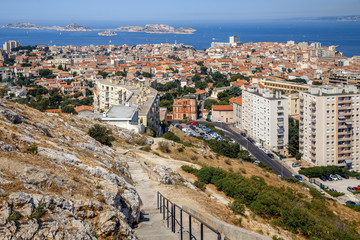 Marseille, France. Aerial panoramic view of the city, the bay and islands from the top of the hill in a summer sunny day. Pathway from the hill down to the city. Holidays in France.
