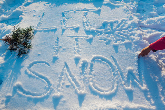 Let it snow writing on fresh snow made by woman outdoors. Winter frosty weather