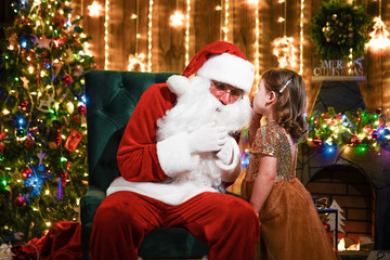 Little girl whispering in Santa's ear. Telling a secret. Revealing the gift you would like to win.