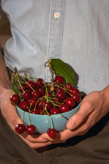 Blue cherry bowl held by a man's hands