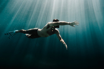 Low angle view of man swimming underwater in ocean