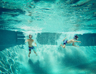 Underwater image of two boys jumping into a swimming pool together.