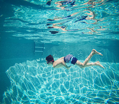 Underwater image of boy swimming in a swimming pool.