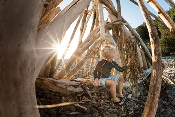 Young boy playing in driftwood structure on a sunny  evening Fotoväggar