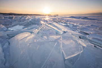 Ice cap and cracks in baikal lake at sunset