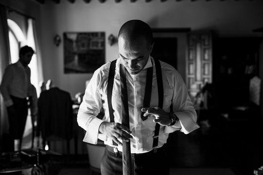 Groom adjusting his tie for wedding