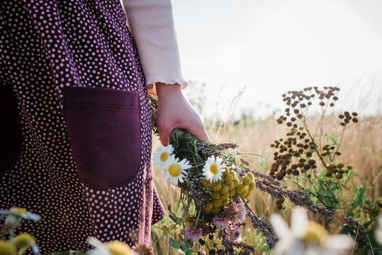 young girls hand holding a bunch of wildflowers in a meadow at sunset