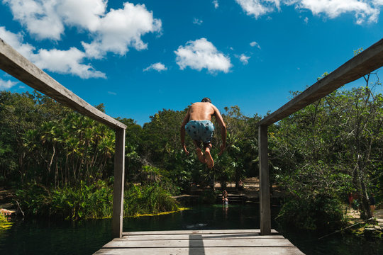 Back view of middle aged male jumping from platform to Cenote Crystal