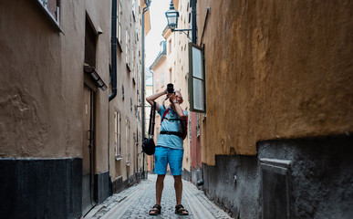 older man taking pictures with a DSLR of the city whilst travelling