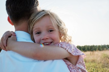 portrait of a young girl being carried by her father at sunset