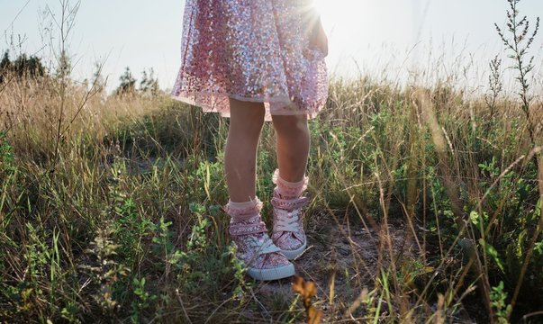 young girls feet and sparkly dress walking through grass at sunset