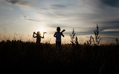 silhouette of brother and sister playing in a meadow at sunset