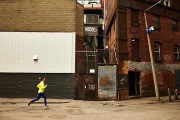 A woman running through an urban city environment.