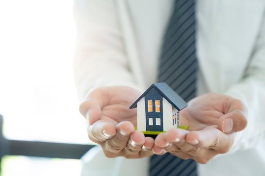Business man hand hold the house model saving small house. House