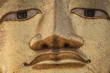 Detail of the giant standing Buddha face at Wat Intharawihan temple