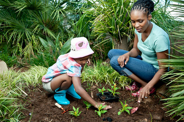 Young African child and her mother working together in the garden