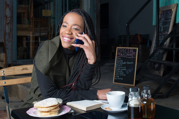 Woman talking on a cellphone at a coffee shop in Johannesburg