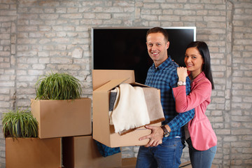Young happy couple move to a new home and unpacking boxes