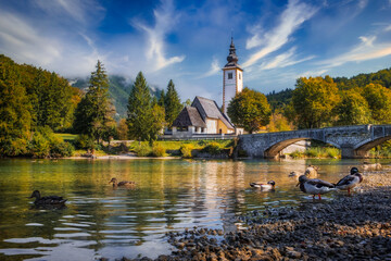 Scenic view of Lake Bohinj church with beautiful colorful foliage, Slovenia