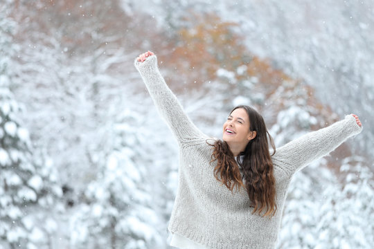 Excited girl enjoying snow in winter raising arms