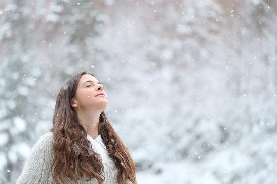 Relaxed girl breathing fresh air enjoying snow in winter