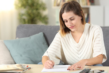 Woman taking notes or filling form at home