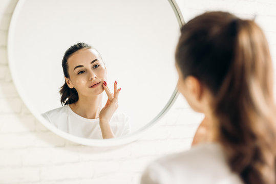 The woman is making up in the bathroom. Woman in bathroom applying cream on face.