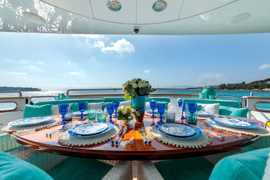 Ocean-themed table setting with blue plates, wine glasses and a flower bouquet on a luxury yacht