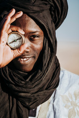Smiling black man with retro compass
